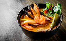 Pan Asian Food. Tom Yam Soup In Black Bowl On Wooden Table Background