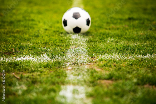 Fototapeta Classic soccer ball, typical black and white pattern, placed on the white marking line of the stadium turf. Traditional football ball on the green grass lawn with copy space. obraz