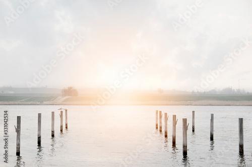 Los postes de madera en el lago al atradecer Canvas Print