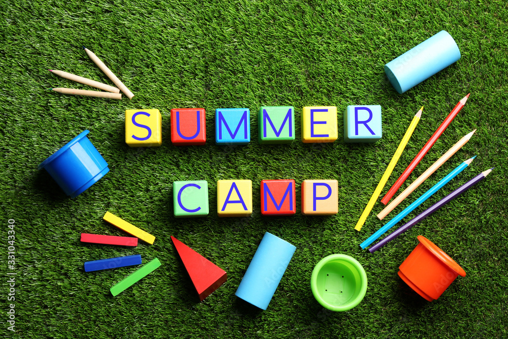 Fototapeta Flat lay composition with phrase SUMMER CAMP made of colorful cubes on green grass