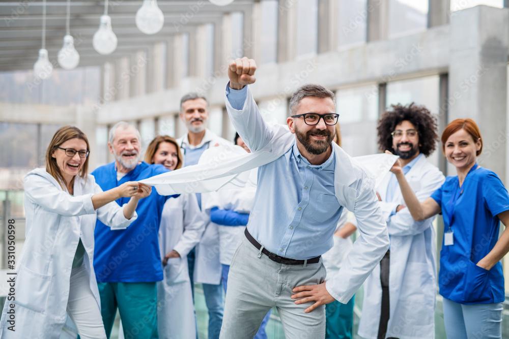 Fototapeta Group of doctors standing in corridor on medical conference, having fun.