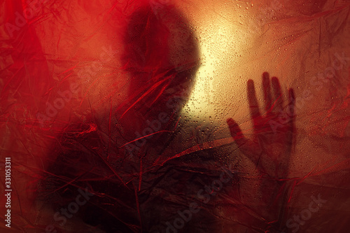 Photo Man's silhouette with hand touching isolation membrane with yellow and red light