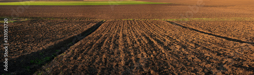 Obraz panorama of plowed field, lines along rural beds and green fields, land for sale - fototapety do salonu