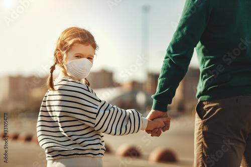 Little girl in medical mask holding hand of father.