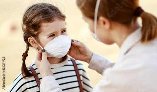 Mother putting on medical mask on daughter. Canvas Print