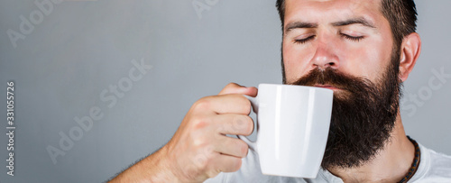 Obraz Portrait male. Closeup tea. Good morning, man holding a cup tea. Morning concept. Handsome bearded male holds cup of coffee, tea. Smiling hipster man with cup of fresh coffee - fototapety do salonu