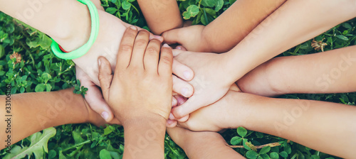 children's hands together on a background of grass. Selective focus.