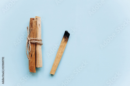 Fototapeta Palo Santo sticks on a blue background. They are used in aromatherapy and religious rites and meditations. obraz