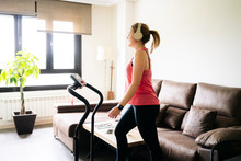 Beautiful Caucasian Blonde Woman Exercises On A Treadmill In Her Living Room