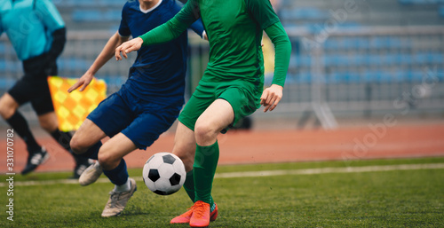 Soccer football players competing for ball and kick ball during match in the stadium Canvas