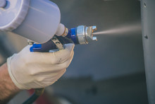 Detail Of A Spray Gun In Action. Applying Lacquer Or Paint Onto Sheet Metal Surface Using A Compressed Air Paint Gun.