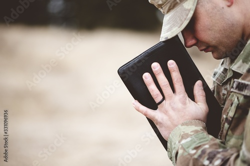 Fotografía Shallow focus shot of a young soldier praying while holding the bible