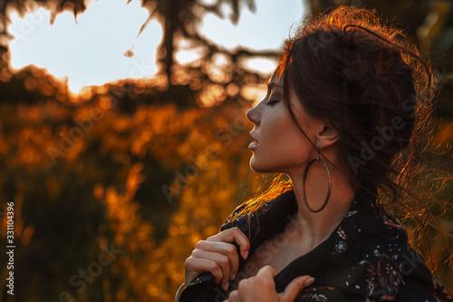 Obraz young stylish woman wearing coat posing outdoors at sunset portrait - fototapety do salonu