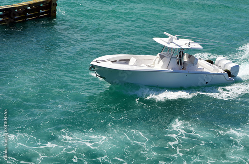 Fotografiet Sports fishing boat with center console powered by three outboard engines