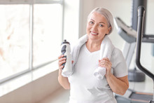 Sporty Mature Woman With Bottle Of Water In Gym