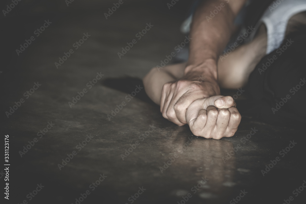 Fototapeta Man's hand holding a woman hand for rape and sexual abuse concept, Wound domestic violence rape, concept photo of sexual assault, International Women's Day