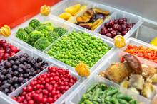 Frozen Fruits And Vegetables. Berries, Mushrooms, Beans And More. Products Are Poured Into Plastic Boxes. In The Center Of The Frame Is Green Peas.