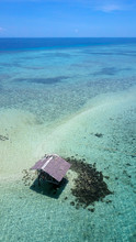 A Dilapidated Thatch Hut On Stilts In The Middle Of A Tropical Sea In The Philippines