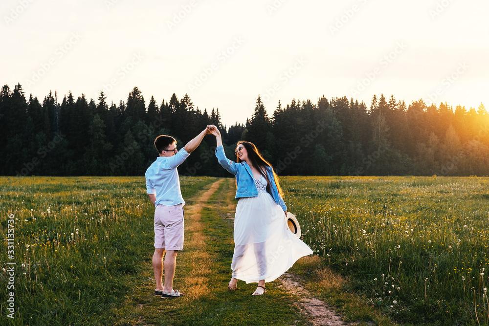 Fototapeta Dancing loving couple in the field. Sunset.