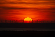 Sun Setting Behind Wind Turbines With Clouds Around