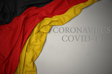 Waving National Flag Of Germany On A Gray Background With Text Coronavirus Covid-19 . Concept.