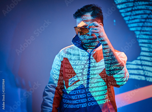 Photo Charismatic and futuristic brunette male model wearing holographic sunglasses and racing blazer posing in neon studio lights of text projection