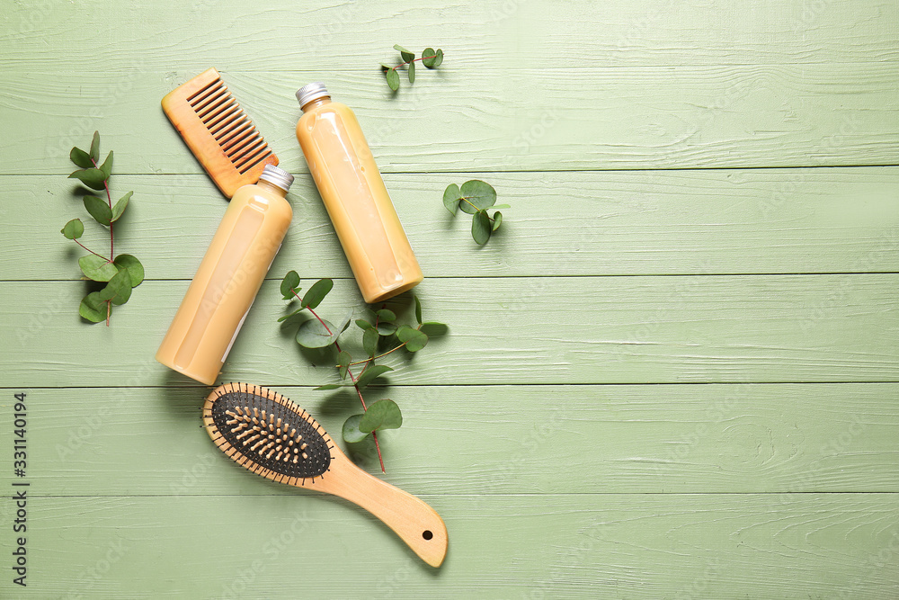 Fototapeta Shampoo with herbal extract, comb and brush on wooden background