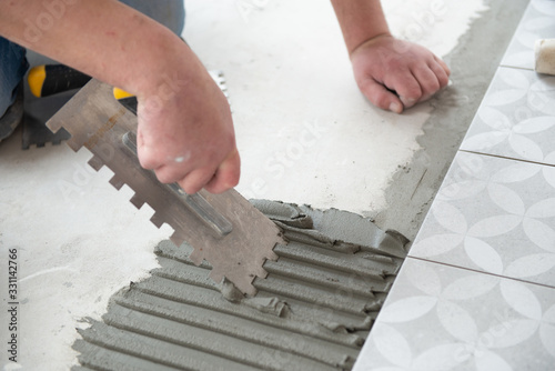 Obraz Tiler laying the ceramic tile on the floor. Professional worker makes renovation. Construction. Hands of the tiler. Home renovation and building new house - fototapety do salonu