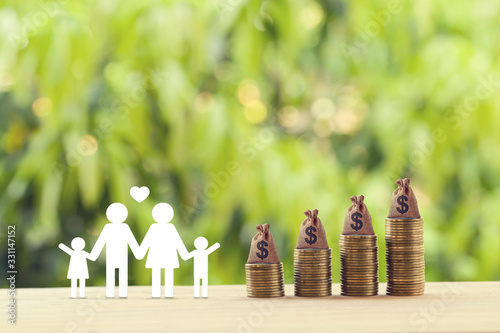 Fototapeta Planning for a secure future and financial status and mitigating taxes concept : Family members, US money bags on rows of rising coins on table. depicts saving for wealth and income growth obraz