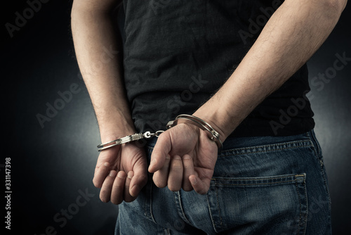 Photo The man is arrested and handcuffed