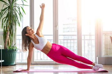 Healthy woman fitness mat doing warmup exercise. Fit woman sitting on exercise mat stretching. Young beautifull woman stretching on the floor. Home training exercises