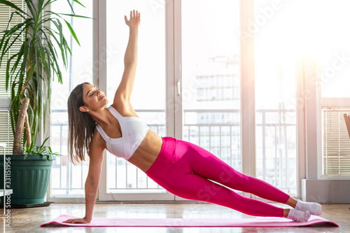 obraz PCV Healthy woman fitness mat doing warmup exercise. Fit woman sitting on exercise mat stretching. Young beautifull woman stretching on the floor. Home training exercises