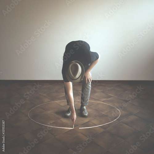 man drawing white circle  around him with chalk, abstract concept Fototapeta