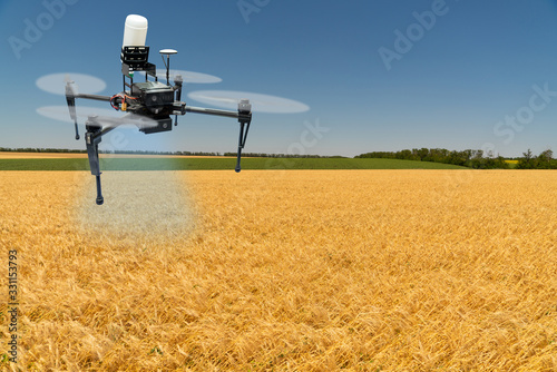 Sticker - Drone sprayer flies over a wheat field. Smart farming and precision agriculture