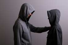 Man And Woman In Hoods Stand B...