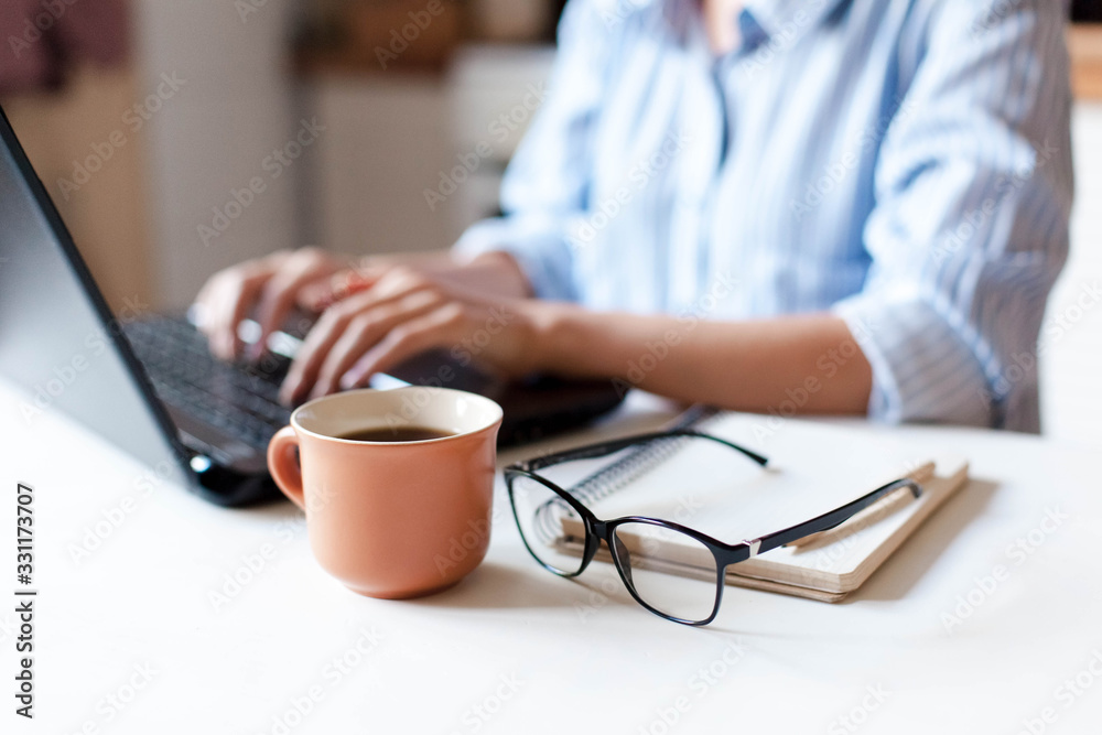 Fototapeta Remote working from home. Freelancer workplace in kitchen with laptop, cup of coffee, spectacles. Concept of distance learning, isolation, female business, shopping online. Close up of woman hands.
