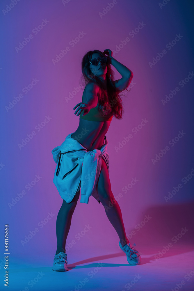 Young woman dancer in stylish youth clothes in sunglasses in gym shoes dancing in a room with bright neon blue-pink color.Girl hipster enjoys a dance in the studio with multi-colored ultraviolet light