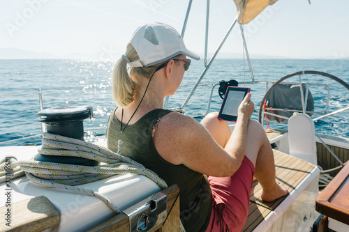 Woman sitting on deck of a yacht enjoying reading in her ebook. Travel and vacation concept.