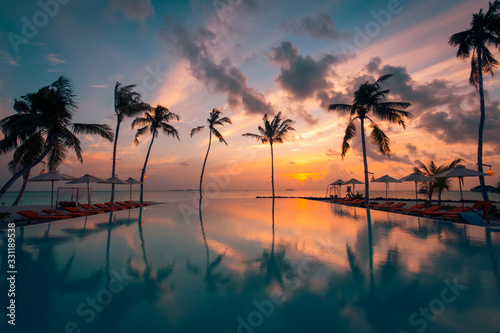 Photo Luxury sunset over infinity pool in a summer beachfront hotel resort at tropical landscape