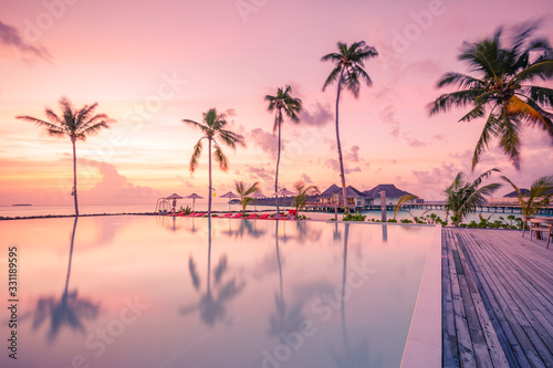 Luxury sunset over infinity pool in a summer beachfront hotel resort at tropical landscape Wallpaper Mural