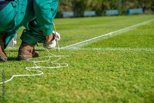 Obraz Stretching a rope for lining a football field using white paint on the grass - fototapety do salonu