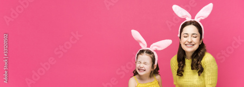 panoramic shot of happy mother and daughter in bunny ears holding easter eggs and laughing isolated on pink