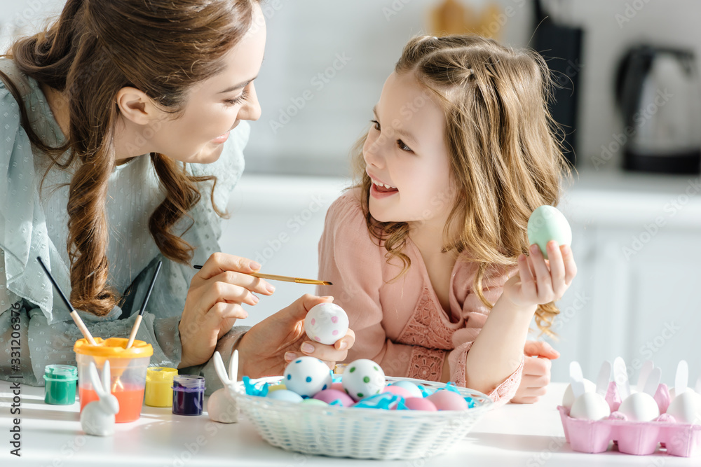 Fototapeta happy mother and cute daughter painting easter eggs