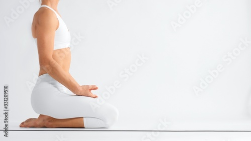 Obraz Unrecognizable woman sits on youga mat in profile in white space  - fototapety do salonu