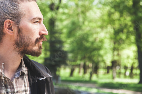 Young adult bearded Asian man, close up profile