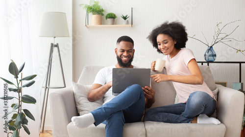 Fototapeta African american couple on couch with laptop obraz