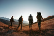 canvas print picture - Four hikers or backpackers walks in sunset mountains