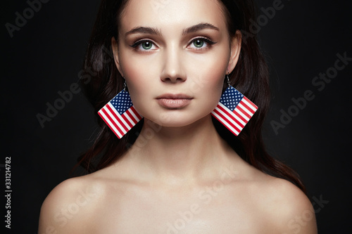 Fotografia Beautiful young woman with american flag earrings