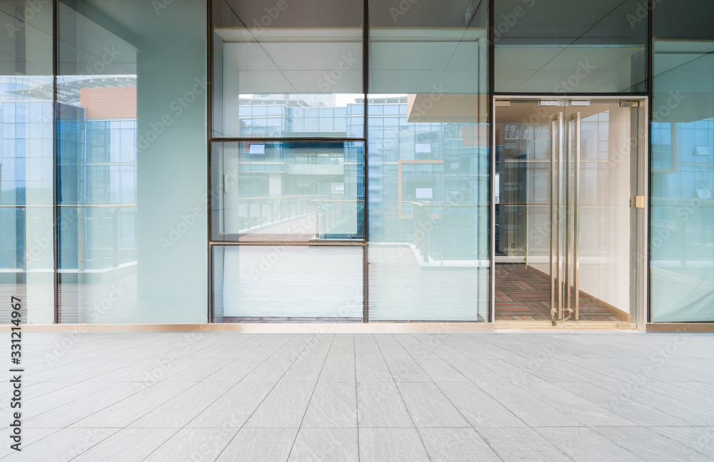 Fototapeta A modern office building with glass doors and windows