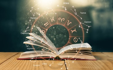 Open book on old wooden table with astrology illustration
